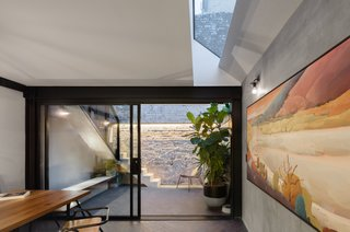 In the courtyard, narrow concrete stairs wrapped in steel filigree leads up to another courtyard located at the rear of the upstairs bedroom.