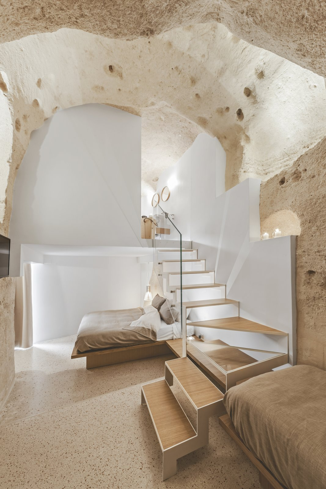 Bedroom, Bed, Wall, and Terrazzo All four guestrooms look like natural grottos with ceilings as high as 15-feet.  Best Bedroom Terrazzo Bed Photos from Stay in This Extraordinary Cave Hotel in Southern Italy