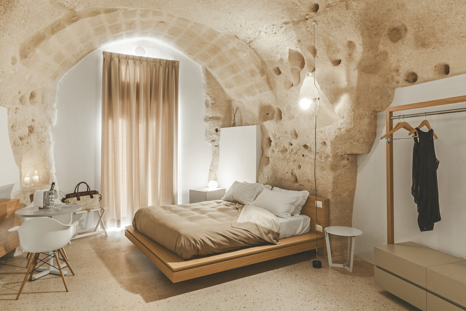 Bedroom, Floor, Night Stands, Table, Bed, Chair, and Terrazzo The plaster was added to sections where the masonry was compromised.  Best Bedroom Terrazzo Bed Floor Photos from Stay in This Extraordinary Cave Hotel in Southern Italy