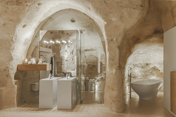 Bath, Pedestal, Freestanding, Stone Slab, Terrazzo, and Wall The spaces are engulfed in tuff and sections of plastered perimeter walls.  Best Bath Terrazzo Wall Photos from Stay in This Extraordinary Cave Hotel in Southern Italy