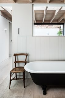 The main bathroom is located off the stairwell. This area has cut-out openings that draw in plenty of light from a courtyard garden sited on the opposite side of the open-tread stairs.