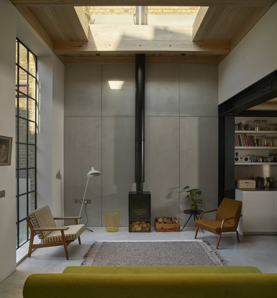 The living spaces on the ground floor now consist of exposed steelwork with polished concrete, timber surfaces, and large Crittall windows.