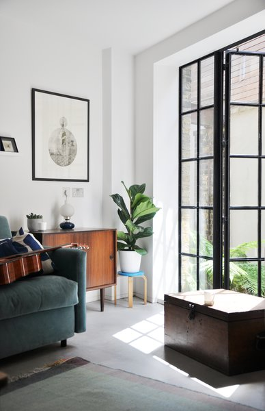 Crittall windows cast playful sun squares along the floors, and deep exposed joists imbue the interiors with a warm golden glow.
