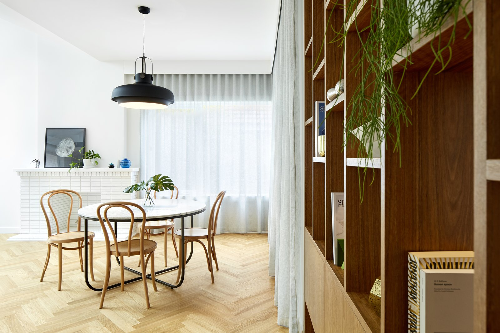 Dining Room, Chair, Pendant Lighting, Light Hardwood Floor, Table, and Standard Layout Fireplace The material and color choices—spotted gum, and clean white and gray—were inspired by the environment of Castlecrag.  Photos from A Renovation Sheds New Light on a Cookie-Cutter Home in Sydney
