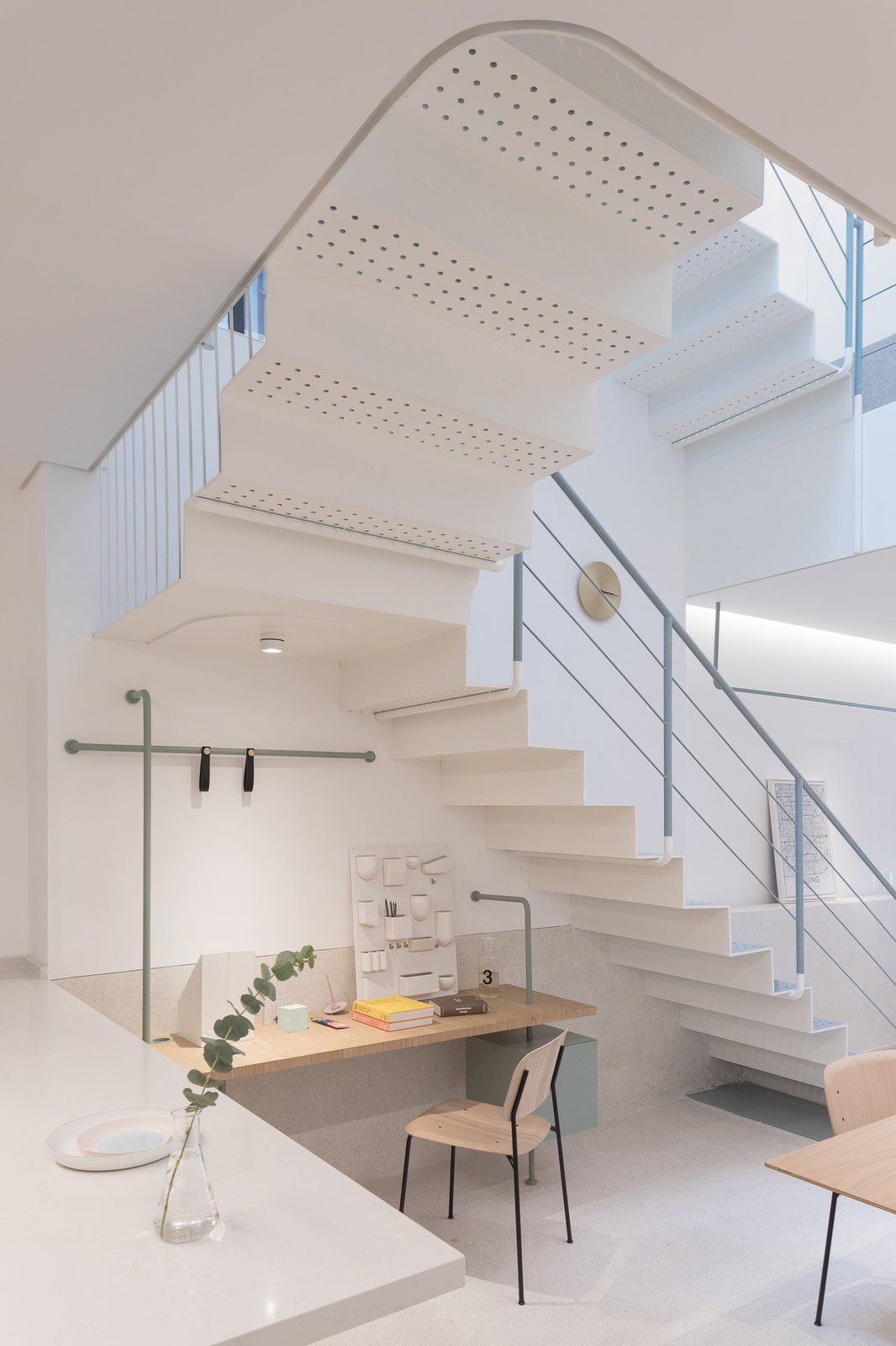 Office, Craft Room, Desk, Lamps, Chair, and Library Perforations in the steel tread of the staircase allow light from the skylight above to filter all the way down to the lower levels.  Best Office Lamps Library Photos from A Sunny Stairwell Brings Light to an Old Shanghai Dwelling