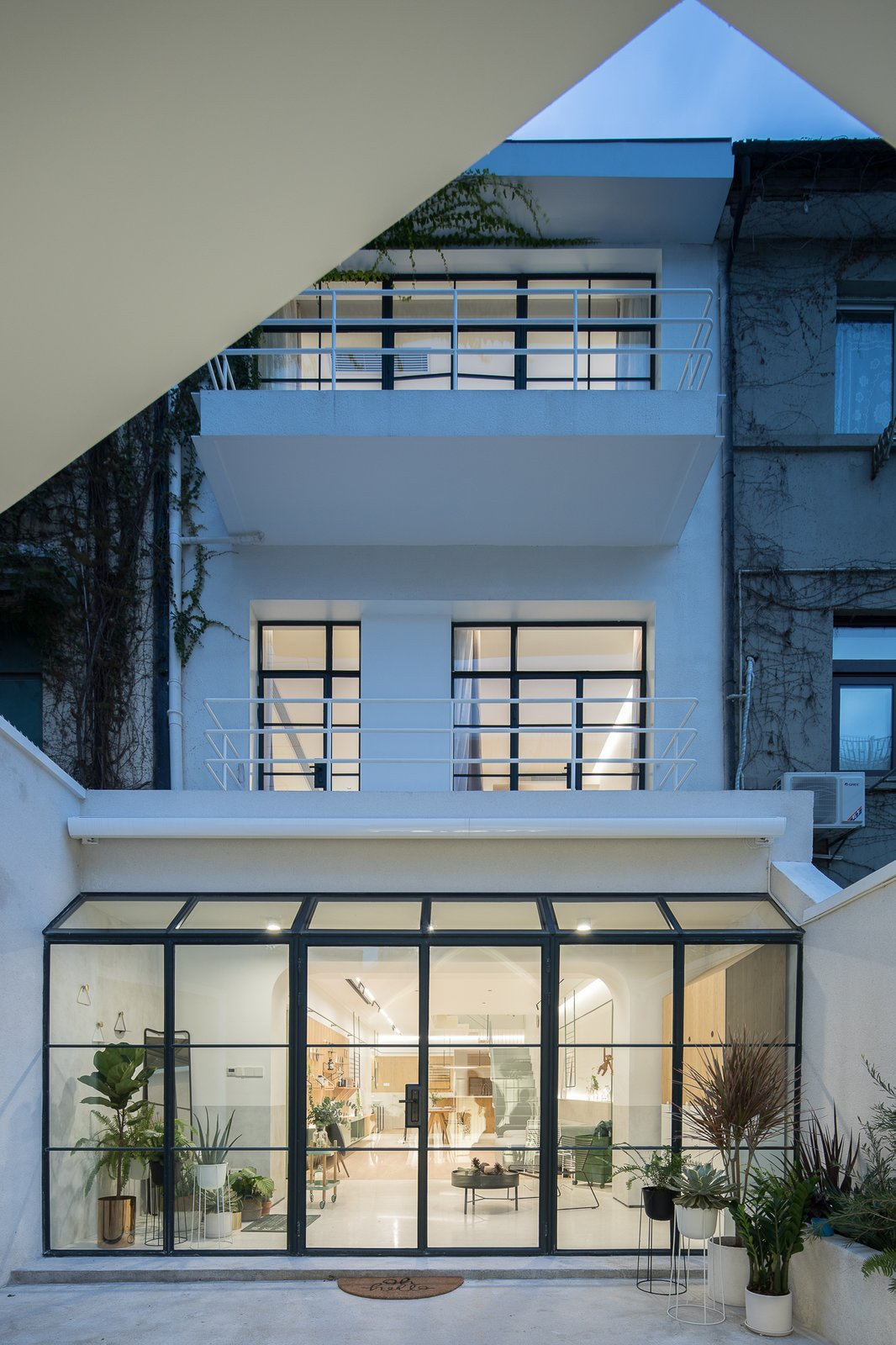 Outdoor, Raised Planters, Small, Vertical, and Back Yard Because of its narrow site and messy interior layout, the original apartment was dark and cramped.  Best Outdoor Vertical Raised Planters Photos from A Sunny Stairwell Brings Light to an Old Shanghai Dwelling
