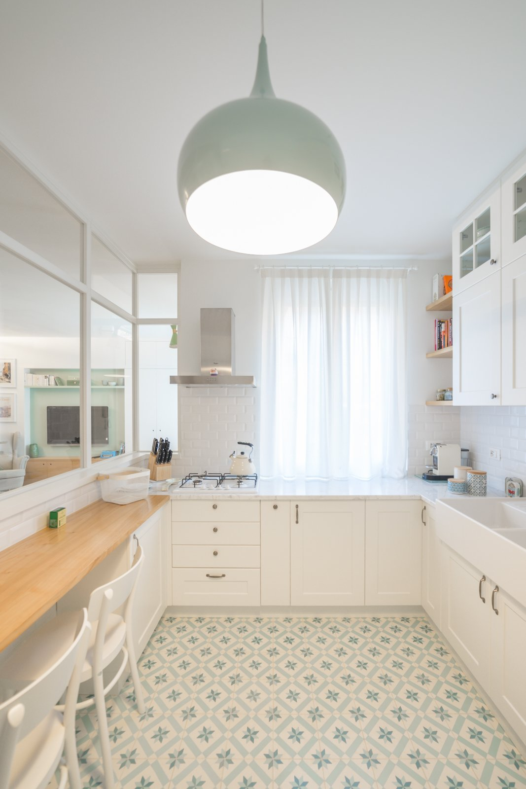Kitchen, Marble, Pendant, Cement Tile, Range Hood, Vessel, and Cooktops Within the kitchen is a discreet, built-in pantry that disappears when not in use.  Best Kitchen Marble Cement Tile Photos from A Revamped Modern Home Is Sprinkled With Old-World Charm