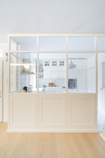 The cozy kitchen is sectioned off by a partially glazed partition walls.