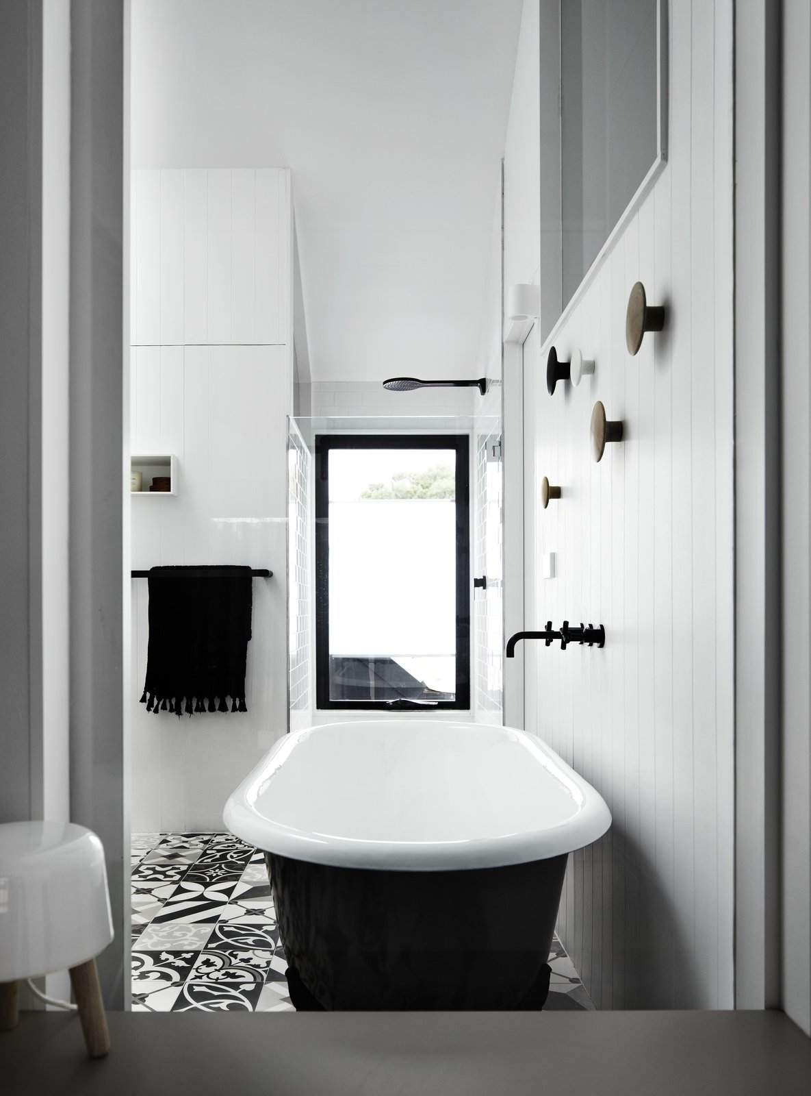 Bath, Freestanding, and Corner The only door in the addition is a repurposed stable door in the ensuite bathroom, which has a freestanding bathtub and monochromatic tiles.     Bath Corner Freestanding Photos from A Melbourne Home Is Treated to a Striking Barn–Like Extension