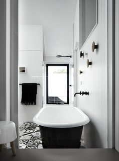 The only door in the addition is a repurposed stable door in the ensuite bathroom, which has a freestanding bathtub and monochromatic tiles.