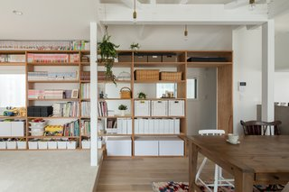 On the second level, part of a structural wall was removed and replaced with built-in plywood shelves to create a permeable partition that encourages visual connectivity between the dining area and the stairs.