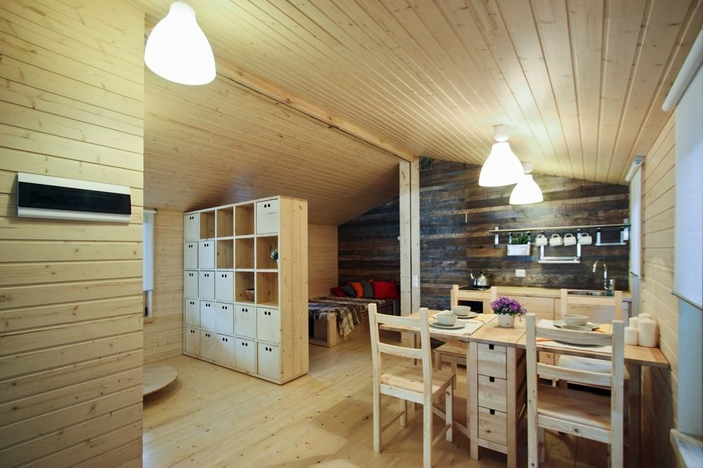 Dining Room, Light Hardwood Floor, Ceiling Lighting, Chair, Storage, and Table Perfect for a holiday retreat, this tiny Dubldom has all the warm wood interiors one would expect of a cabin in nature.  Photo 8 of 22 in DublDom Prefab Homes Can Be Built in One Day