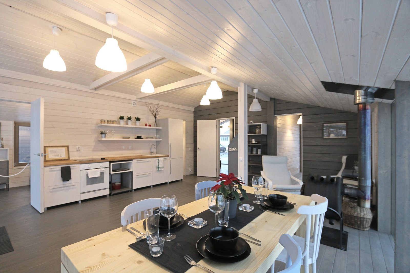 Dining Room, Ceiling Lighting, Wood Burning Fireplace, Chair, and Table Starting at $63,922, this model has two bedrooms, insulated floors, and triple-glazed windows.  Photo 15 of 22 in DublDom Prefab Homes Can Be Built in One Day