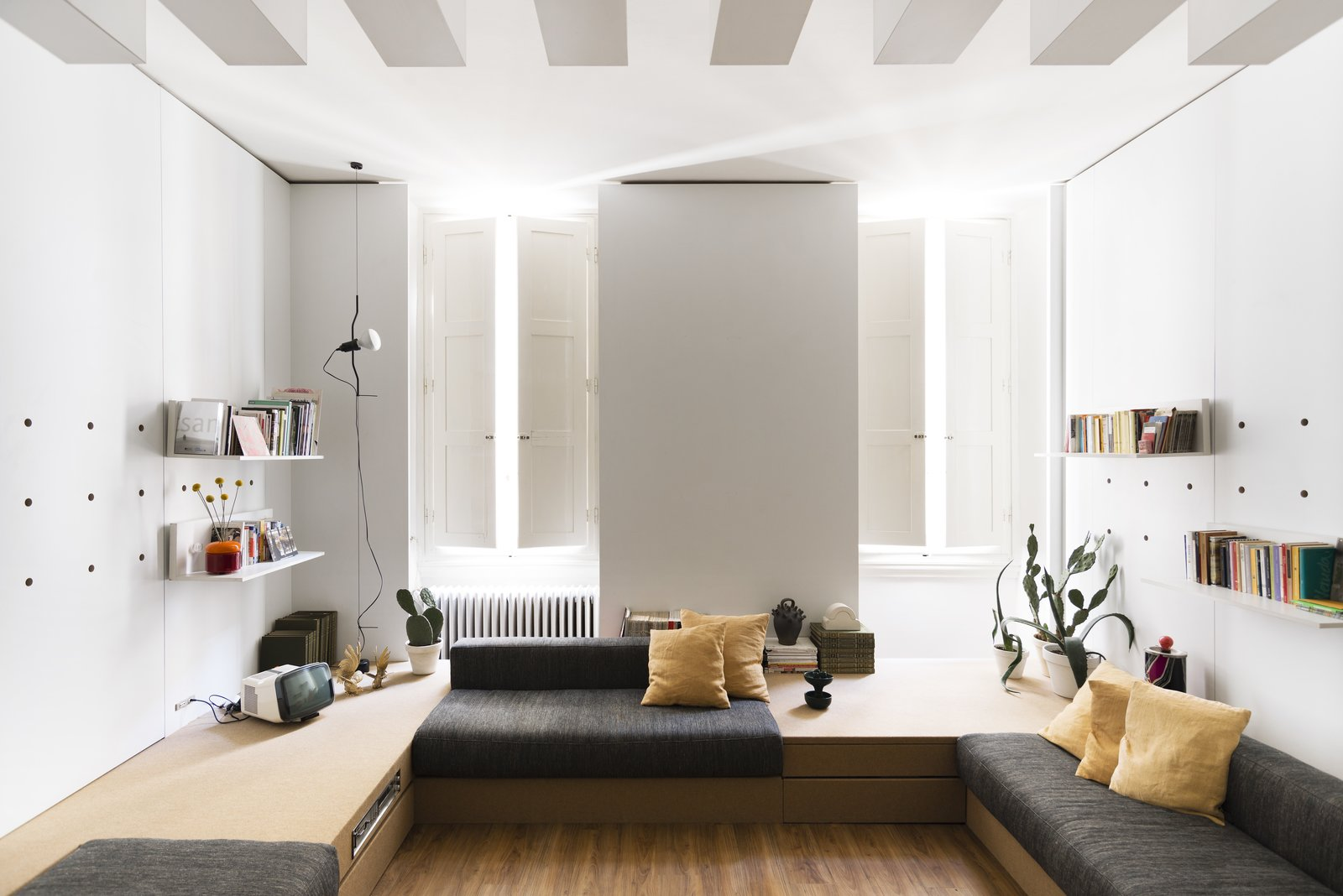 Living Room, Sofa, Medium Hardwood Floor, Bench, Shelves, and Pendant Lighting In the main living area are built-in platforms with storage spaces and niches that can be filled with padding to create sofas or beds.   Best Photos from A Tiny Florence Flat Is Reborn as an Architect's Live/Work Space