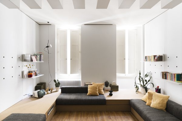 To add more space to her petite Florence apartment originally designed by Roberto Monsani, architect Silvia Allori incorporated fold-down furniture and storage into the white laminate walls that also support bookshelves.