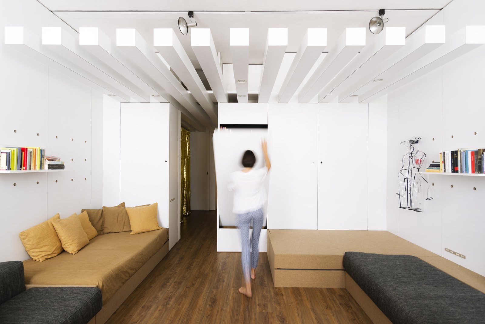Living, Sofa, Bench, Shelves, Medium Hardwood, and Track Slim, white, brise soleil-like beams run along the length of the ceiling in the mid-section of the apartment.  Best Living Track Shelves Photos from A Tiny Florence Flat Is Reborn as an Architect's Live/Work Space