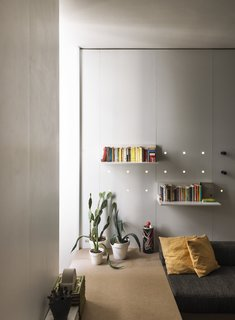 Neon lights are fitted within a series of perforations in the white laminate to break up the rigid geometry of the space.