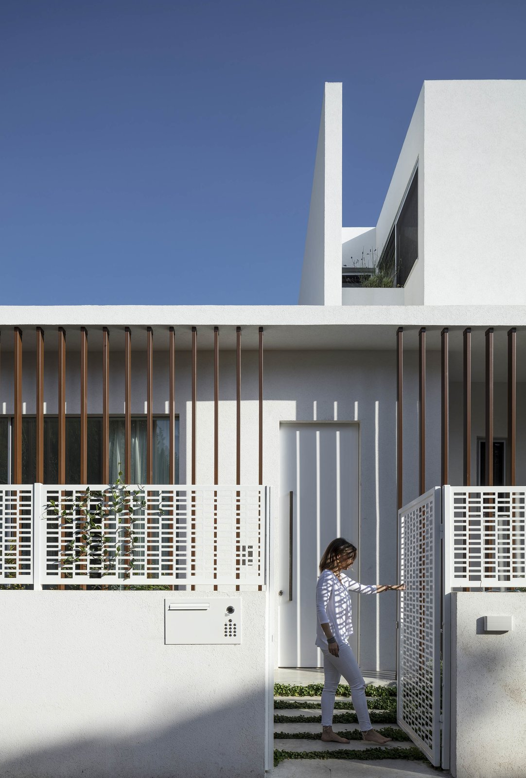 Doors, Metal, Exterior, and Swing Door Type The pattern of the decorative screen for the stairs is repeated on the fence that surrounds the house.    Photo 3 of 19 in Sleek Concrete Cubes Form This Pavilion-Like Home in Israel