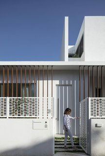 The pattern of the decorative screen for the stairs is repeated on the fence that surrounds the house.