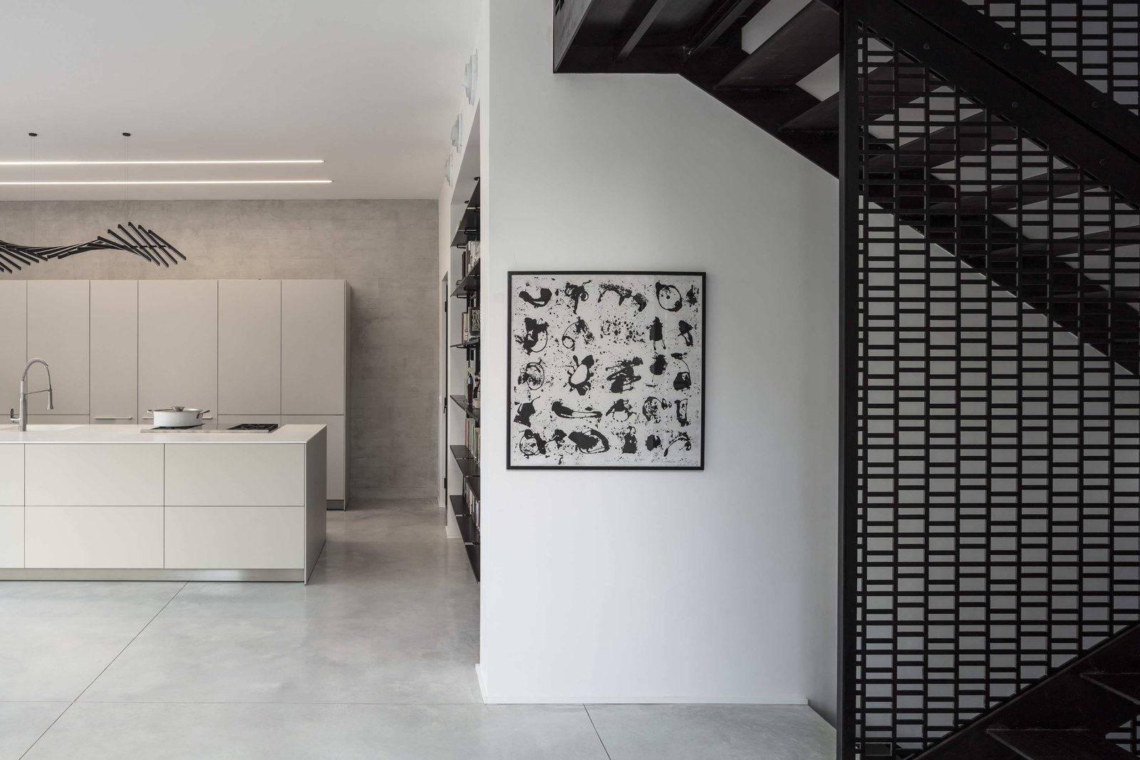 Staircase, Metal Tread, and Metal Railing Carefully selected furniture items—by brands such as Desalto, Living Divani, and Ligne Roset—work together to complement the paired-back, elegant design of the residence.    Photo 11 of 19 in Sleek Concrete Cubes Form This Pavilion-Like Home in Israel