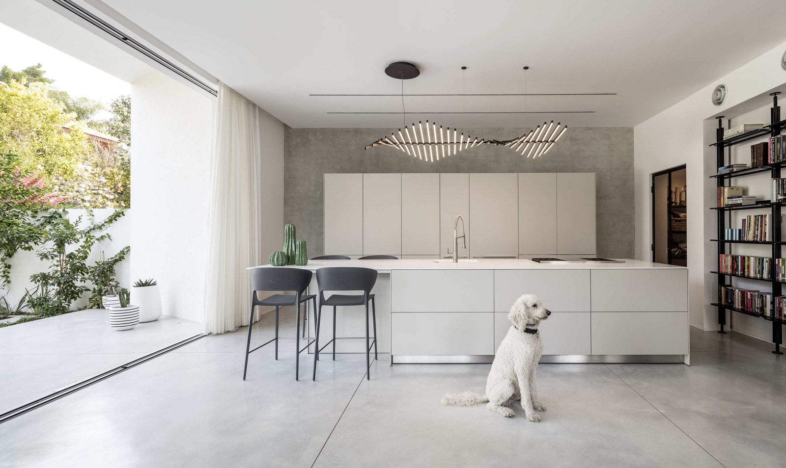 Kitchen, White Cabinet, Concrete Floor, Drop In Sink, Pendant Lighting, and Range The open interior of white walls and polished concrete floors echoes the restrained aesthetics of the façade.    Photo 7 of 19 in Sleek Concrete Cubes Form This Pavilion-Like Home in Israel