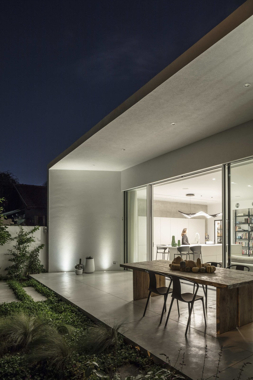 Outdoor, Grass, Shrubs, Landscape Lighting, Back Yard, Large Patio, Porch, Deck, and Concrete Patio, Porch, Deck At the back of the house, a glazed wall slides open to connect with a spacious green terrace.    Photo 15 of 19 in Sleek Concrete Cubes Form This Pavilion-Like Home in Israel