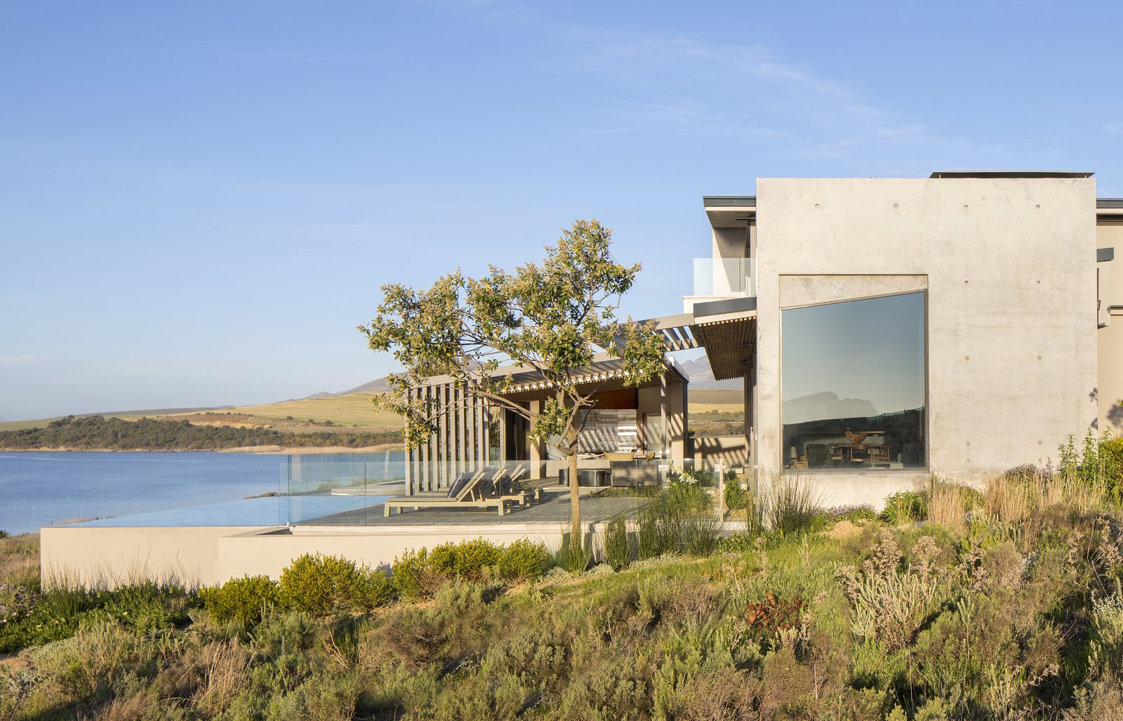 Exterior, House Building Type, Concrete Siding Material, Metal Roof Material, Flat RoofLine, Wood Siding Material, and Shed RoofLine The roofs are made of corrugated aluminum, and the timber sidings used at the entrance are repeated on key ceiling planes.    Best Photos from An Elegant South African Home Embraces Mesmerizing Views