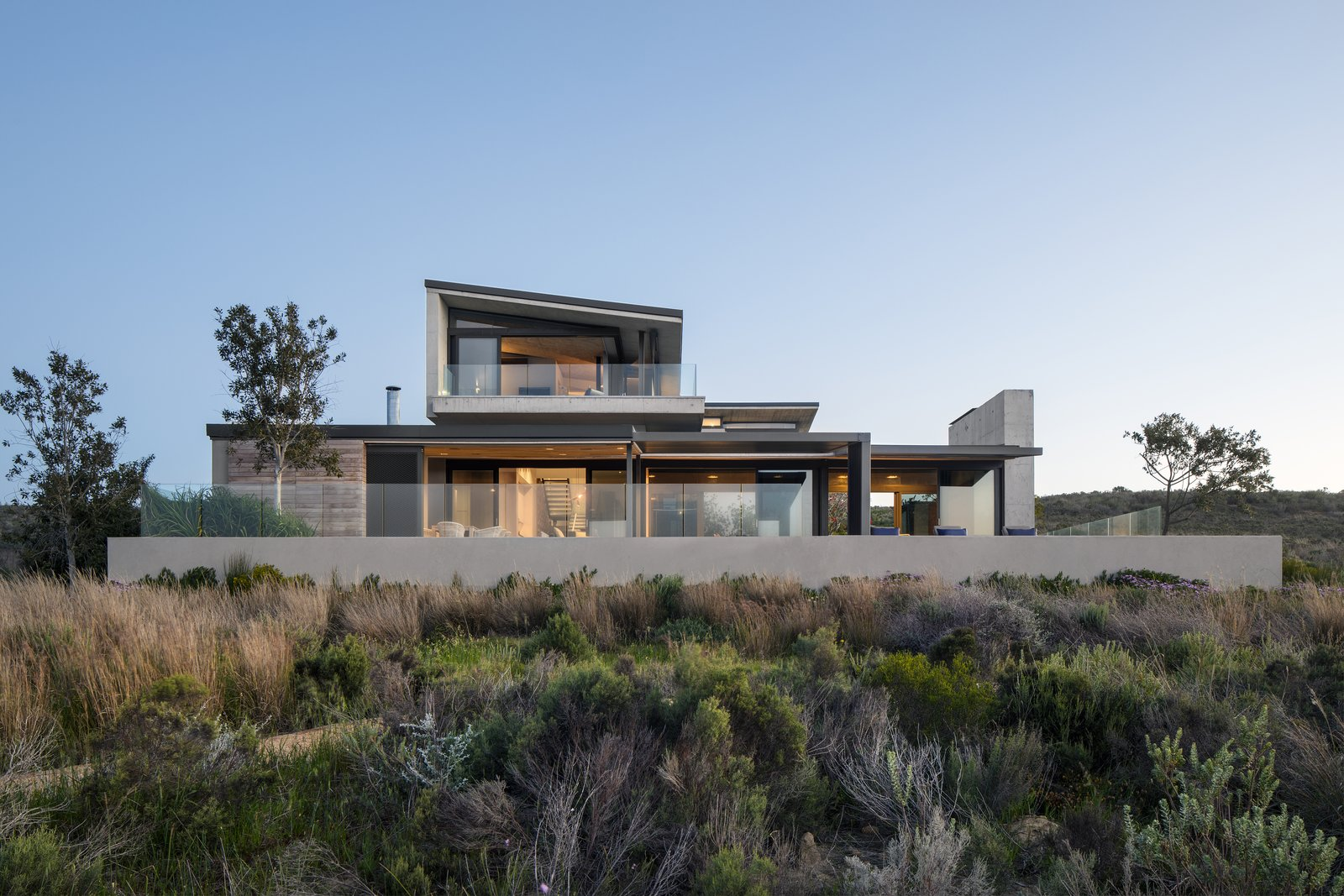 Exterior, House, Metal, Concrete, Wood, Flat, and Shed The owner wanted a cozy family escape with plenty of outdoor entertaining areas.    Best Exterior Shed Flat Concrete Metal Photos from An Elegant South African Home Embraces Mesmerizing Views