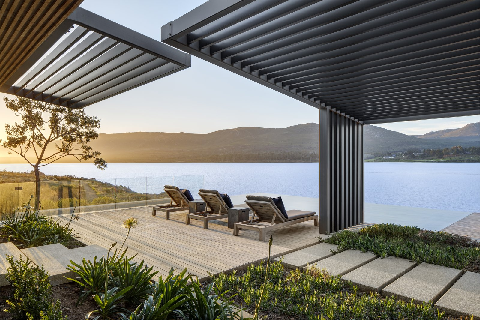 Outdoor, Walkways, Large, Shrubs, Slope, Wood, Side Yard, and Gardens Robust and low-maintenance metal mesh—which offers both solar and privacy control—has been chosen for the screens.      Outdoor Side Yard Slope Photos from An Elegant South African Home Embraces Mesmerizing Views