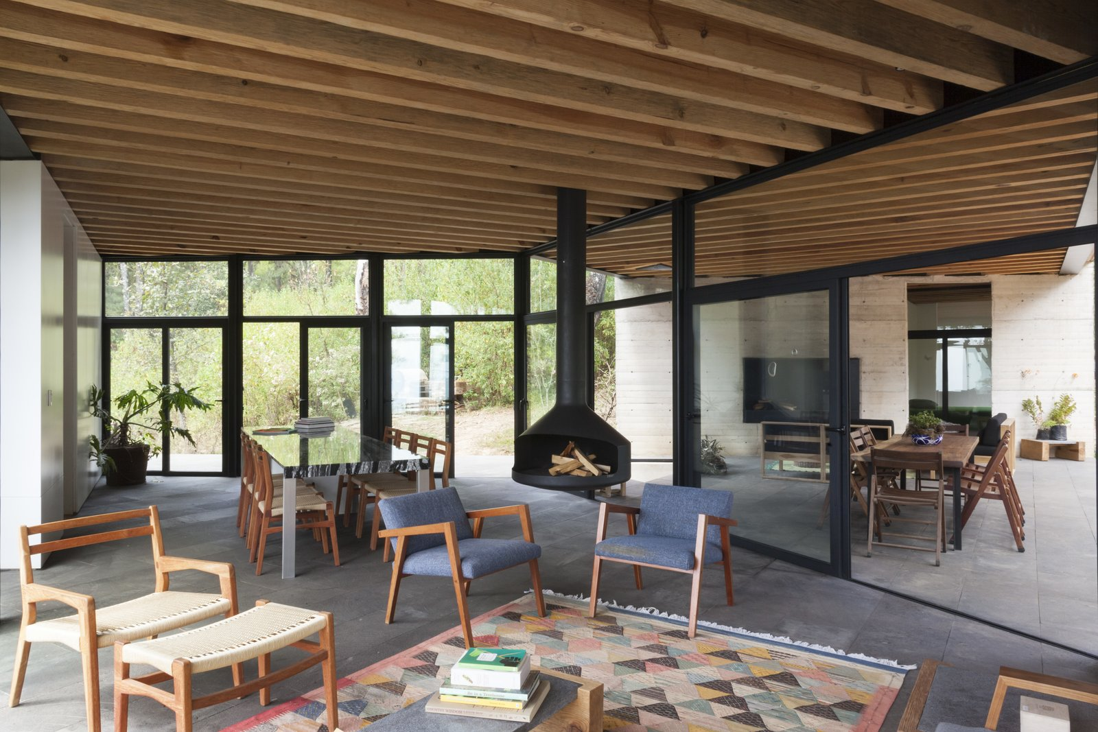 Living, Chair, Coffee Tables, Hanging, Ottomans, Concrete, Rug, and Table The ceiling beams have been left exposed to create a stark contrast with the black framing.  Best Living Hanging Table Photos from Upcycled Trees Cloak This Modern Mexican Home