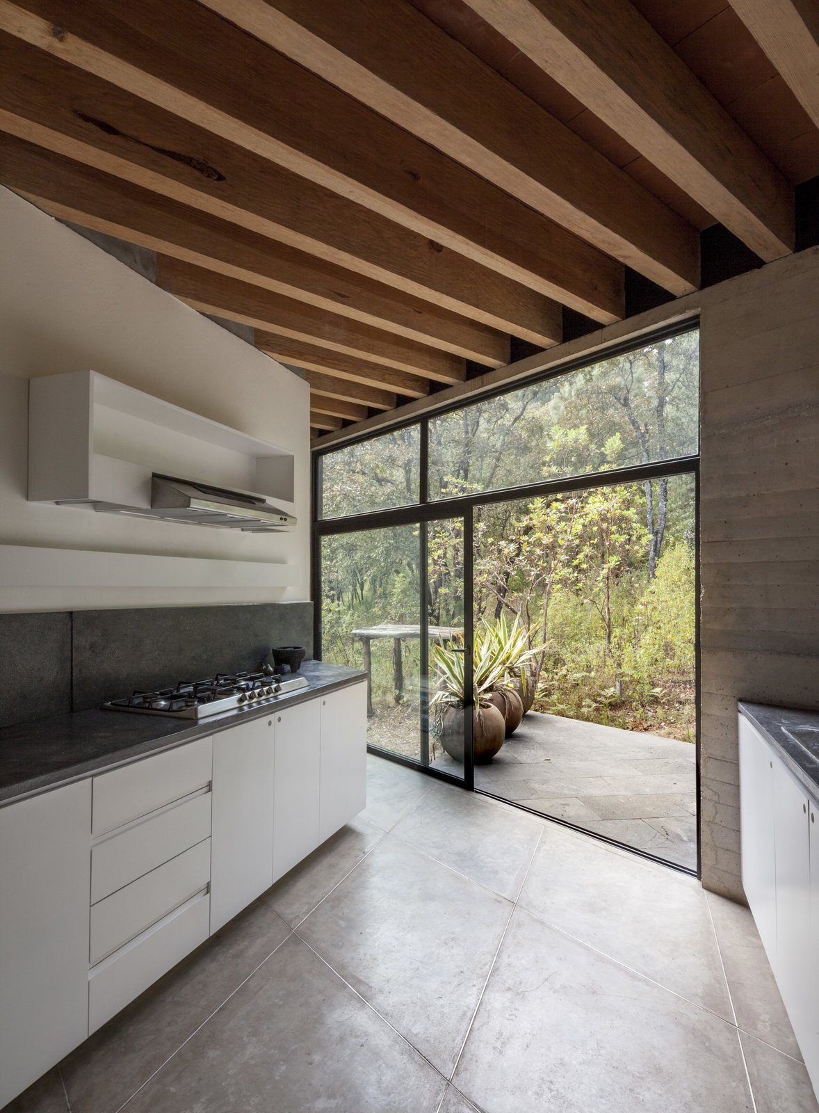 Kitchen, Cooktops, White, Concrete, Concrete, Concrete, and Range Hood The kitchen features a sleek, modern design.  Best Kitchen Concrete Cooktops Photos from Upcycled Trees Cloak This Modern Mexican Home