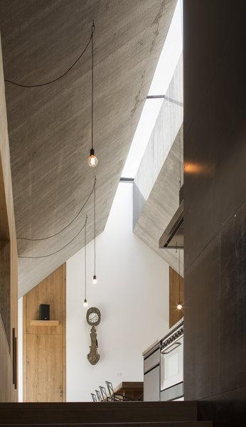 """""""The ridge of the roof is pushed apart, creating a continuous skylight that runs throughout the house's linear volume and provides top light for all the crucial spaces,"""" says Dekleva."""