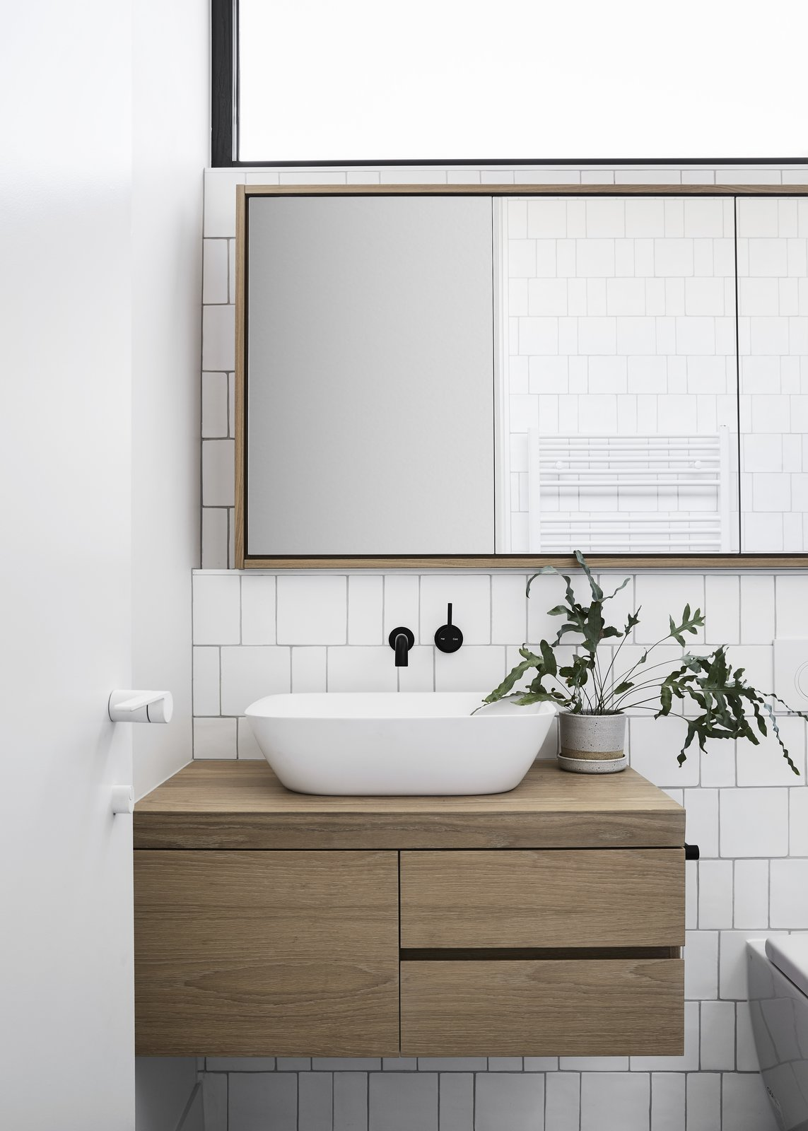 Bath Room, Vessel Sink, Wood Counter, and Ceramic Tile Wall A new bathroom is located just before a step down to the living areas.    Best Photos from A Historic Melbourne Home Is Respectfully Modernized For a Young Family