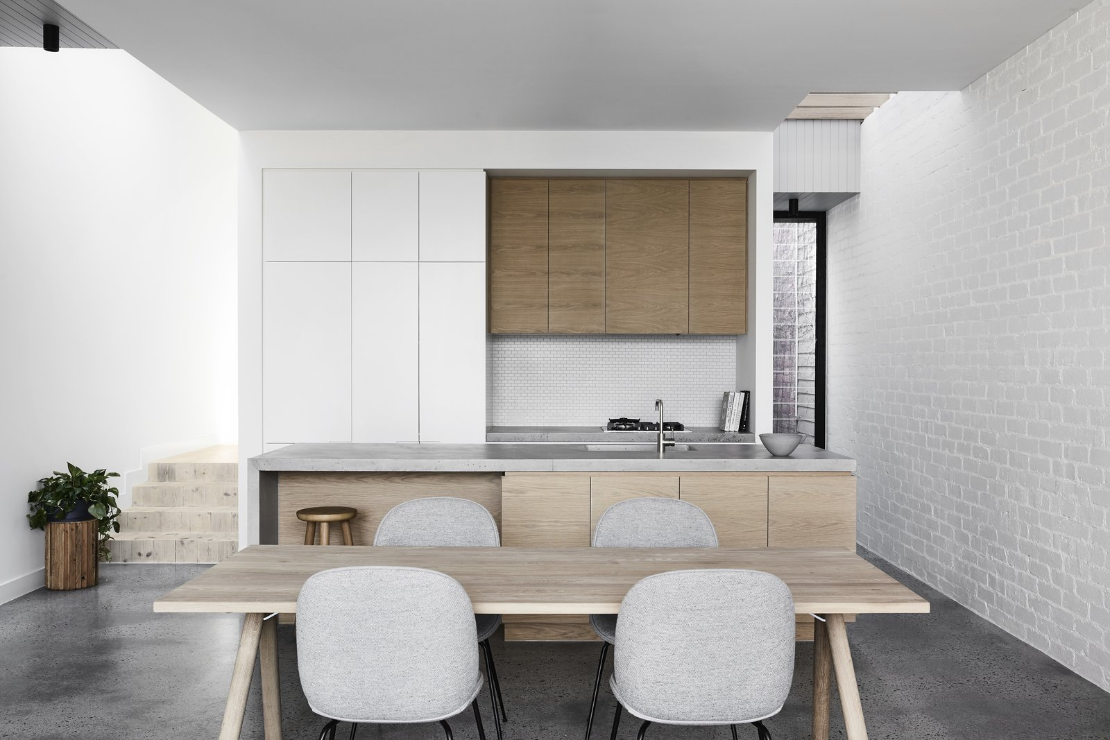 Kitchen, Wood, Concrete, White, Concrete, Cooktops, Ceiling, and Undermount A simple color palette of gray, white, and brown gives the home a sleek, Scandinavian-inspired vibe.    Best Kitchen Concrete Concrete Photos from A Historic Melbourne Home Is Respectfully Modernized For a Young Family