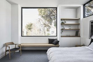 The bedroom on the upper level features a strategically placed window that frames vistas of the mountains and beyond.