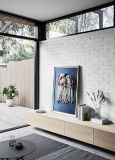 Washed oak joinery and textured tiles add warmth to the space, providing a soft contrast to the crisp concrete and brick.