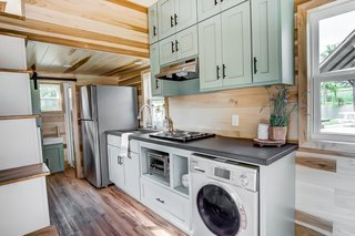 The kitchen includes a four-burner stovetop, convection oven, fridge/freezer, washer/dryer, sink, breakfast bar, and custom cabinetry.