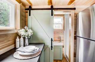 Behind a sliding barn-style door is a bathroom with a shower and toilet.