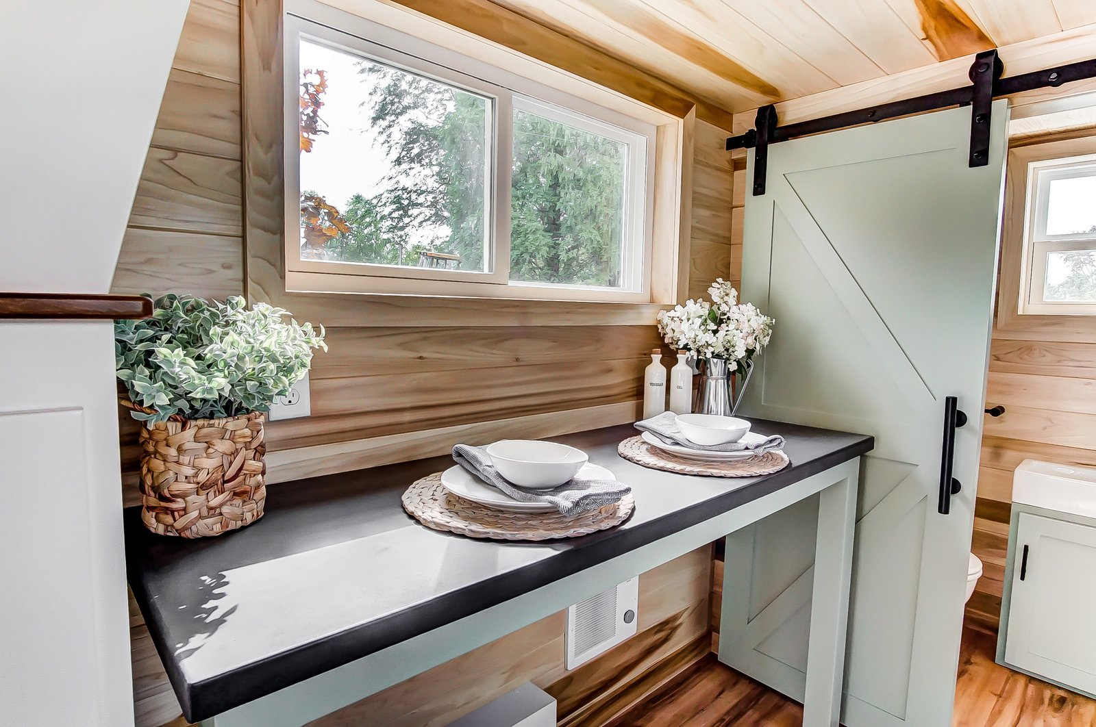 Dining Room, Table, and Medium Hardwood Floor The Clover's interior walls are finished in poplar wood, and its floors are covered in vinyl.    Photo 7 of 11 in This 270-Square-Foot Tiny Home Is Now Up For Grabs at $89K