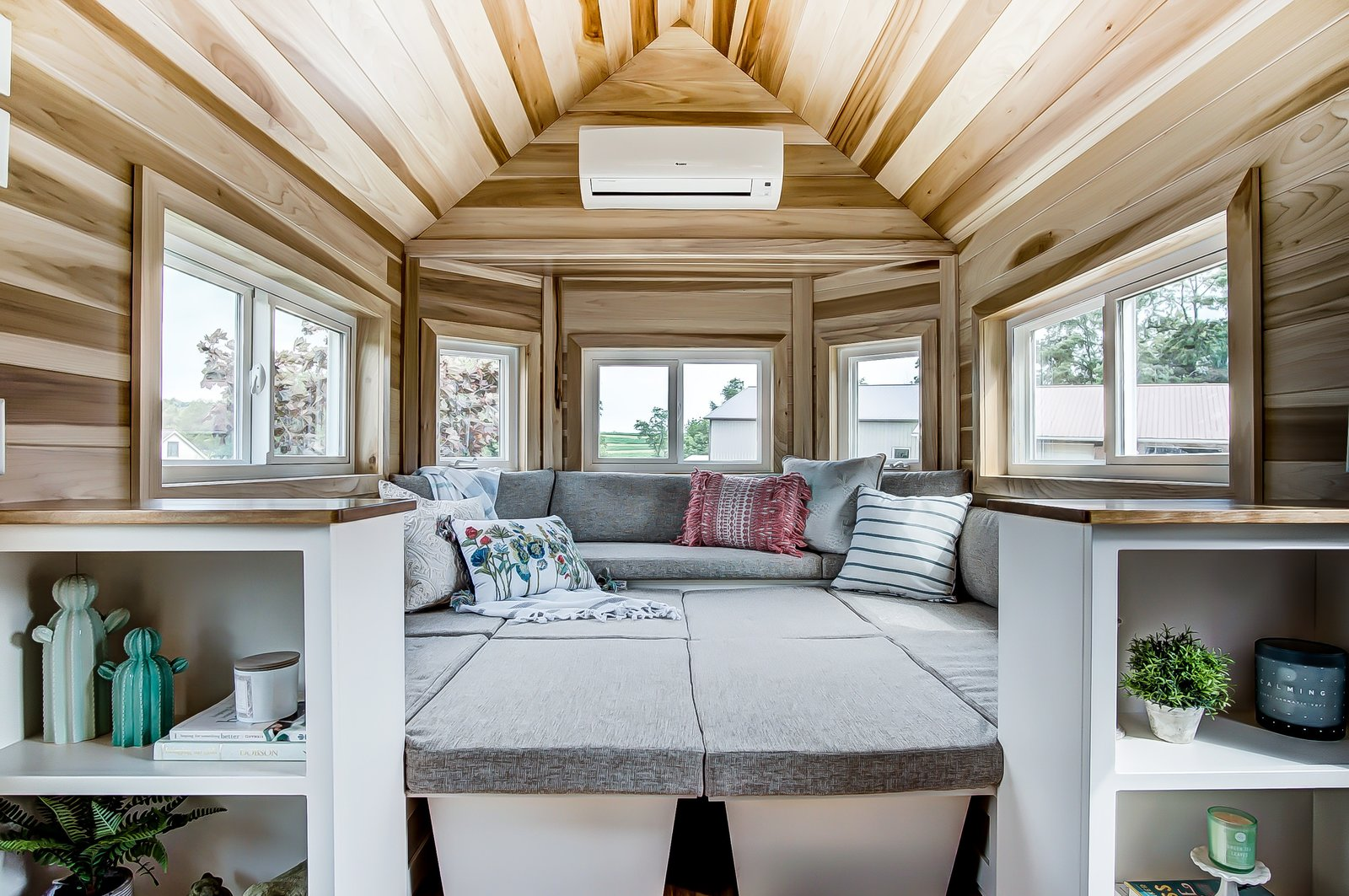 Living Room, Shelves, Sofa, and Bench The living room is designed as an elevated U-shaped sitting lounge. This space is surrounded by windows that draw in plenty of natural light.    Photo 3 of 11 in This 270-Square-Foot Tiny Home Is Now Up For Grabs at $89K