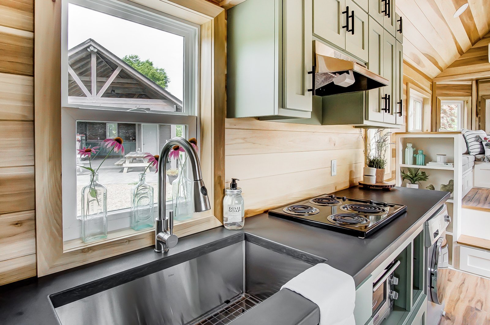 Kitchen, Wood Backsplashe, Concrete Counter, Cooktops, Colorful Cabinet, Range Hood, Medium Hardwood Floor, and Undermount Sink Concrete countertops and poplar wood finishings give the interiors a warm, cozy feel.    Photo 5 of 11 in This 270-Square-Foot Tiny Home Is Now Up For Grabs at $89K