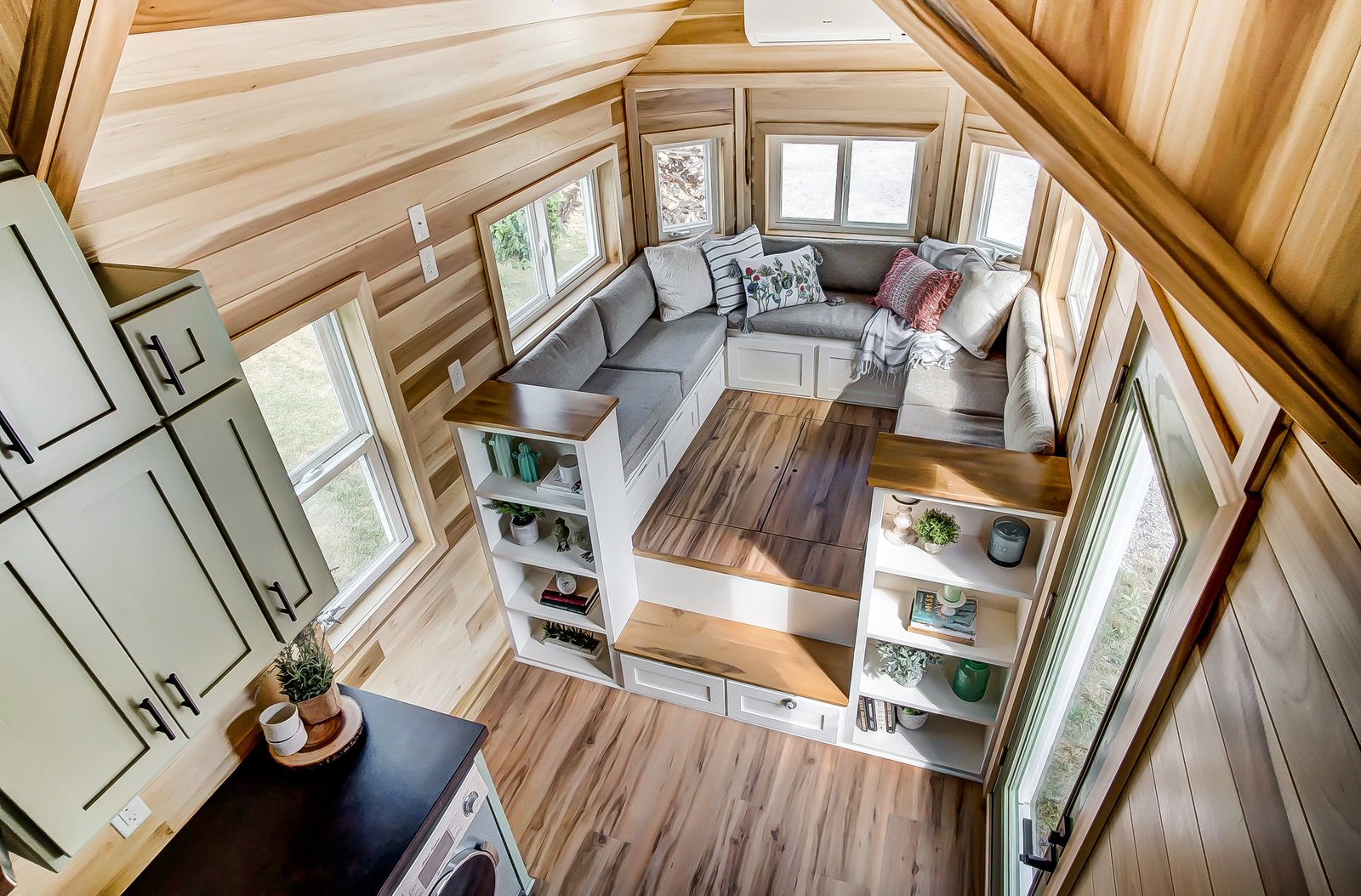 Living Room, Bench, Storage, Shelves, Medium Hardwood Floor, and Sofa There is plenty of built-in storage and shelves for books along the walls.    Best Photos from This 270-Square-Foot Tiny Home Is Now Up For Grabs at $89K