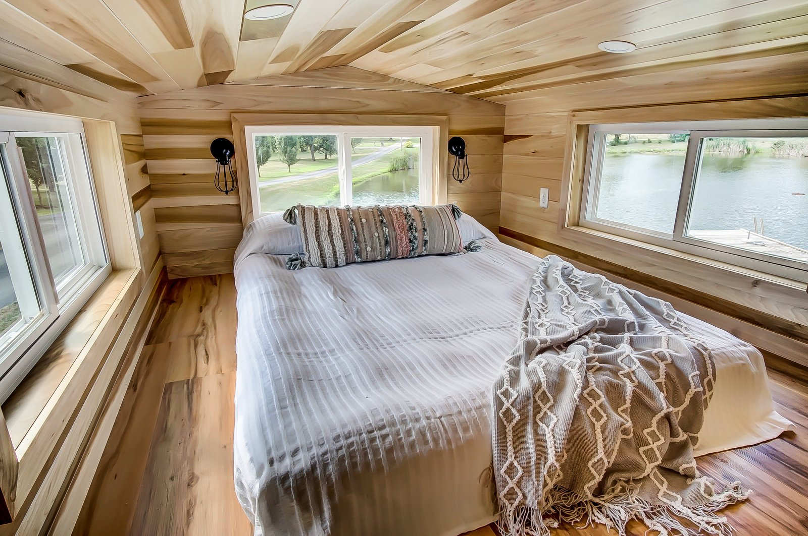 Bedroom, Bed, Medium Hardwood Floor, Wall Lighting, and Recessed Lighting Steps lead up to a sleeping loft that can accommodate two people on a double bed.    Photo 8 of 11 in This 270-Square-Foot Tiny Home Is Now Up For Grabs at $89K