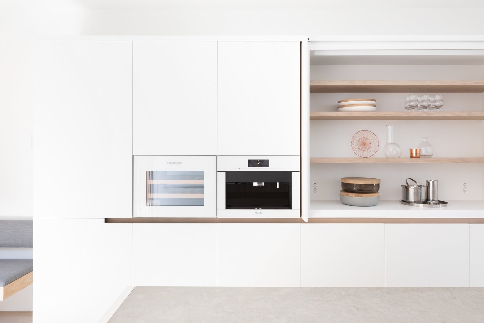 Kitchen, Wall Oven, Wine Cooler, and White Cabinet In the kitchen, white lacquer millwork is complemented by white glass.    Best Photos from 11 Skylights Brighten a Compact, Narrow Home in Vancouver