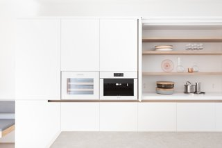 In the kitchen, white lacquer millwork is complemented by white glass.