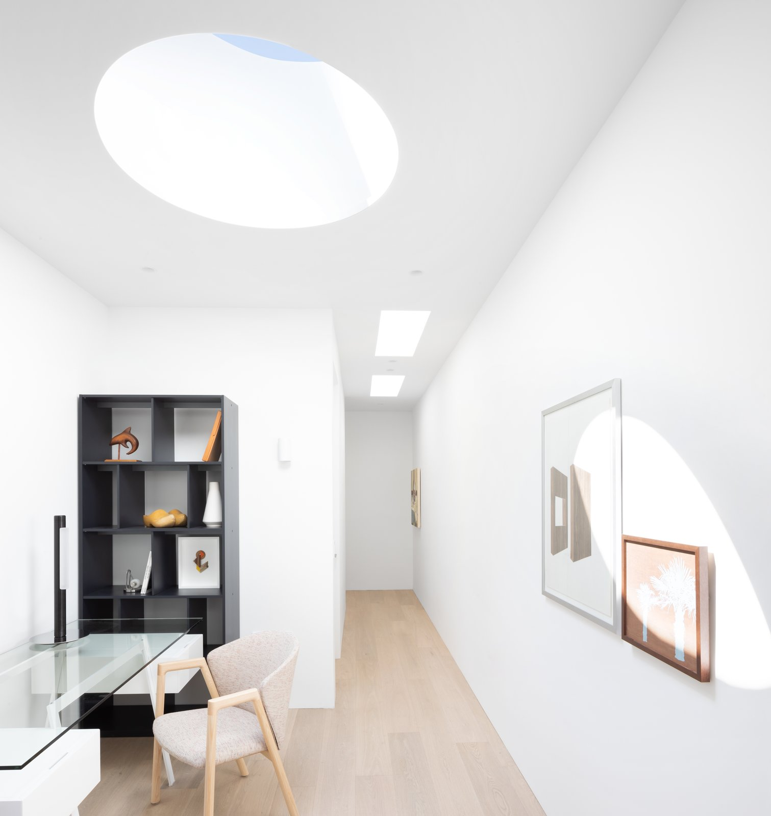 Office, Bookcase, Study Room Type, Library Room Type, Chair, Light Hardwood Floor, and Desk A crisp palette of toned woods and fresh white paint give the indoor and outdoor spaces a light and open feel.    Best Photos from 11 Skylights Brighten a Compact, Narrow Home in Vancouver