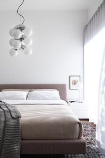 If you need bedroom lighting ideas for the ceiling, check out how this tonal bedroom in Vancouver utilizes a modern pendant light to add visual interest while tying perfectly with the desk lamp.