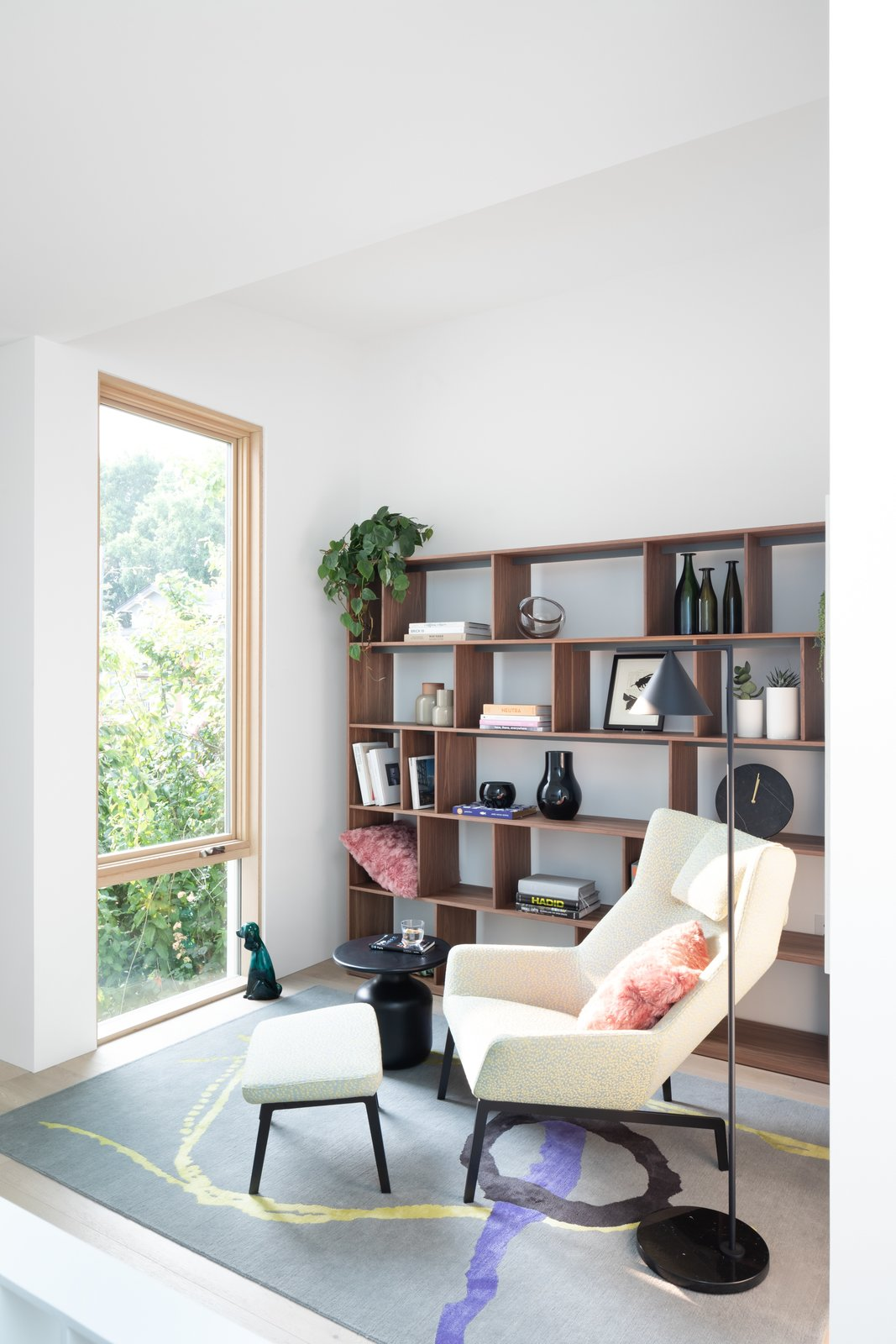Living Room, Ottomans, Shelves, Chair, End Tables, Floor Lighting, and Rug Floor A Bensen chair and shelves, along with a Diurne carpet from Salari, sit in the den.    Photos from 11 Skylights Brighten a Compact, Narrow Home in Vancouver