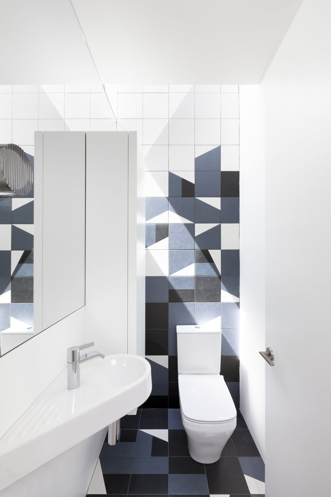 Bath Room, Wall Mount Sink, and Two Piece Toilet Mutina tiles have been used for the floor and walls in the kids' bathroom.     Best Photos from 11 Skylights Brighten a Compact, Narrow Home in Vancouver