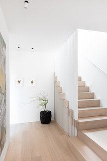 A staircase with Nordic Oak treads and a slatted steel guardrail.